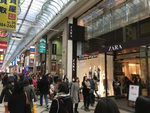 商店街を歩いて右手側にZARAが。次の交差点をZARAとは反対側の左に曲がって下さい。